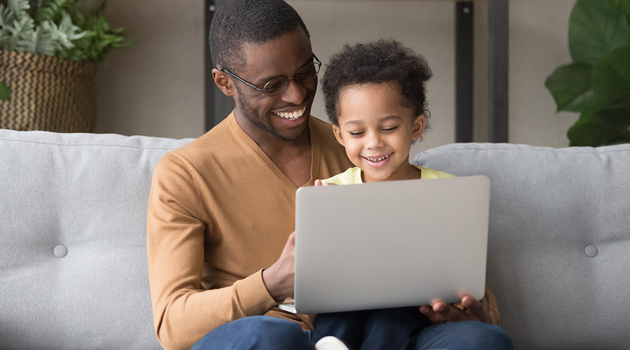 Man with small child on lap looking at laptop computer