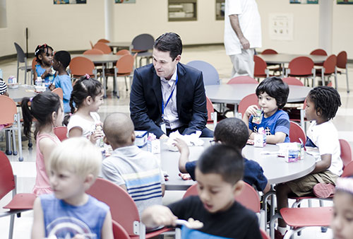 Dr. Marty Pollio sits at a lunchroom table talking with elementary kids