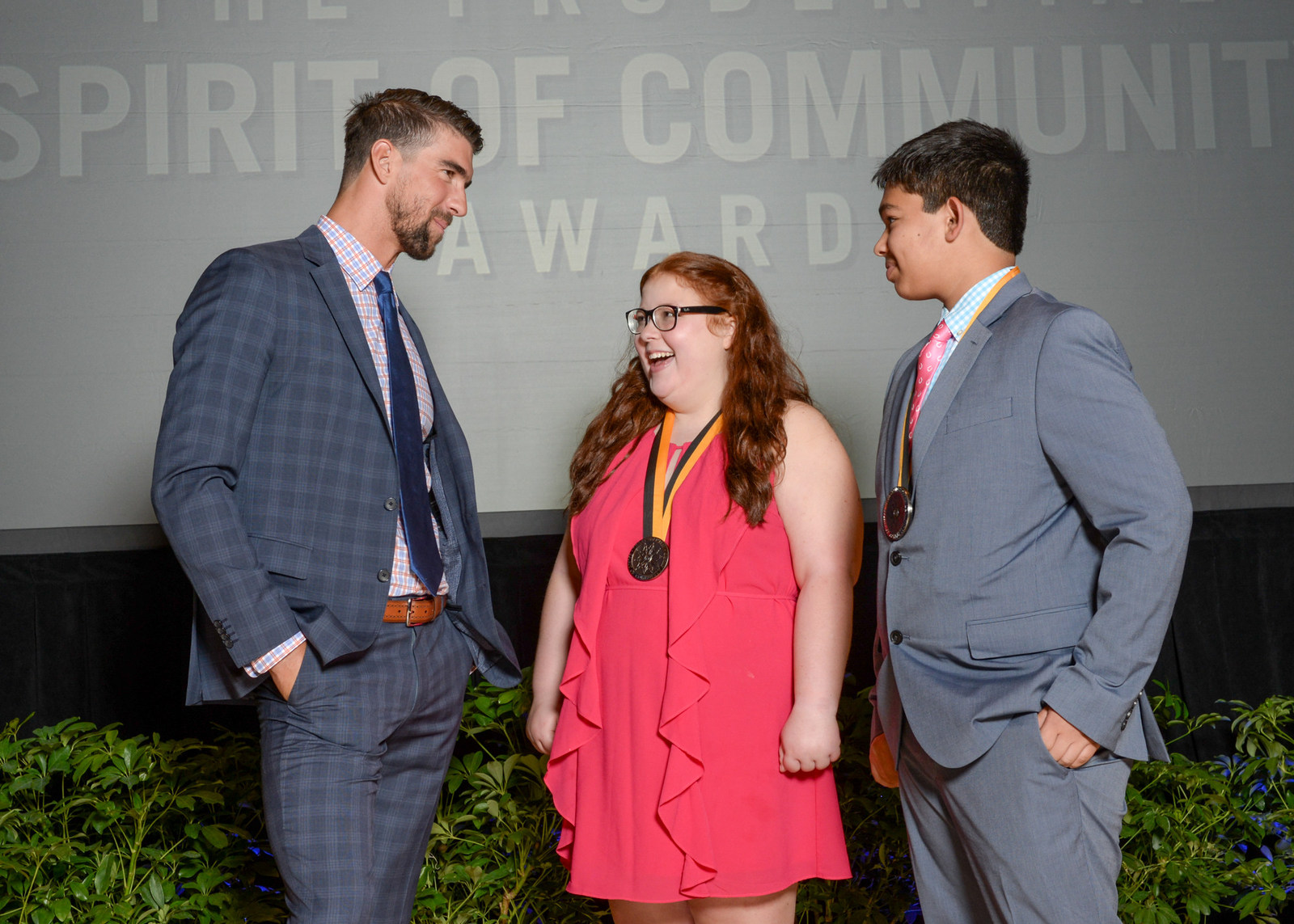 Olympic gold medalist Michael Phelps congratulates Anna-Maria Beck, 17 (center) and Andrew Dunn, 14 (right), both of Louisville, on being named Kentucky's top two youth volunteers for 2017 by The Prudential Spirit of Community Awards.