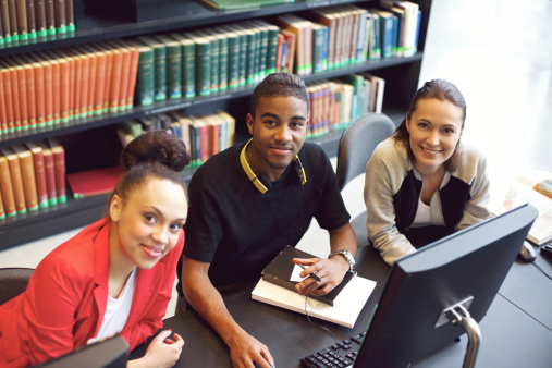 Three students sitting at table in library working at computer